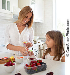 Woman cooking macarons at the kitchen with her little...