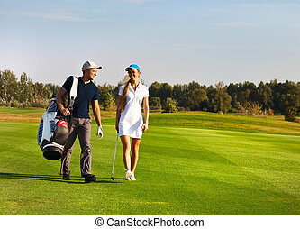 Young sportive couple playing golf on a golf course walking...