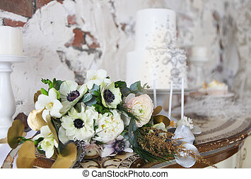 Wedding cake with silver decoration and wedding bouquet with...