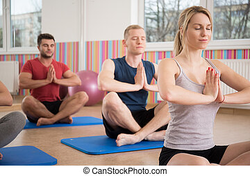 Yoga class - People sitting in lotus position during yoga...
