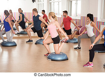 Bosu training at the gym - Athletic people during bosu...