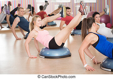 Abs exercise on the bosu - Gym people doing abs exercise on...
