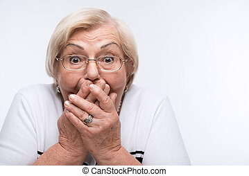 Elderly woman closes her mouth, ears and eyes with hands -...