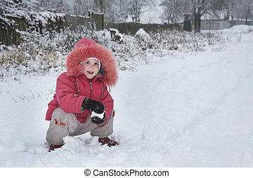 Little girl in winter on the street sculpts snowball.