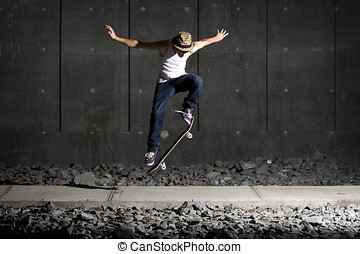 Skateboarder doing an ollie on walking path with concrete...