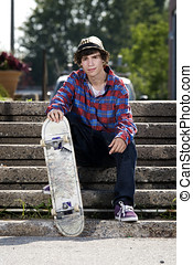 Teenage skateboarder sitting on stairs looking at camera
