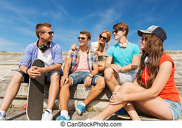 group of smiling friends sitting on city street -...