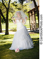 beautiful bride on a green grass in wedding day