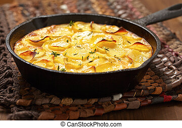 scalloped potatoes in a rustic iron skillet