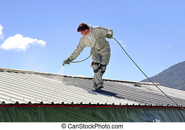 painting the roof - A trademan uses an airless spray to...