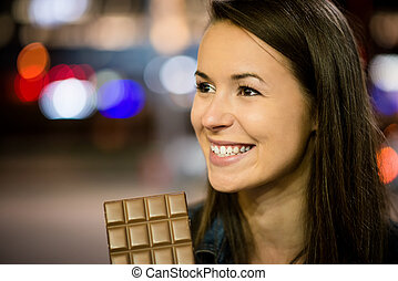 Woman eating chocolate - Young woman eating chocolate in...