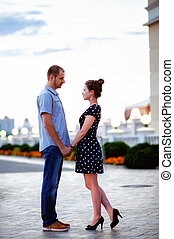 Couple holding hands in the background of city