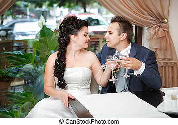 Closeup portrait of bride and groom drinking champagne at...