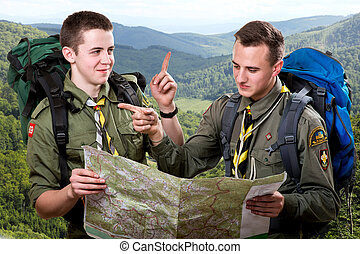 Scout tour - Two young scout boys with backpacks holding the...