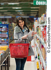 Woman Reading Her Shopping List In The Supermarket -...