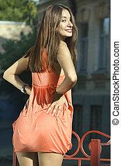 back of brunette in coral dress