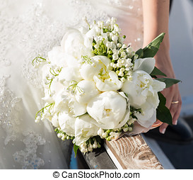 Bride holding wedding bouquet with white peonies