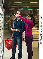 Couple At Groceries Store - Beautiful Young Couple Shopping...