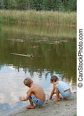 kids feeding ducks - two kids playing on the lakecoast and...