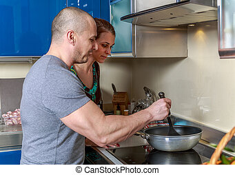 Woman looking into a pan her husband is holding in a kitchen