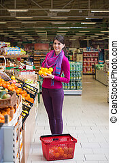 Smiling Woman Buying Dairy Products In Supermarket -...