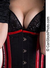 Close-up shot of busty fetish woman in corset and bra