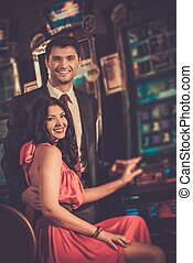 Beautiful couple near slot machine in a casino