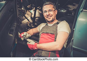 Cheerful mechanic with wrench fixing something in a car interior