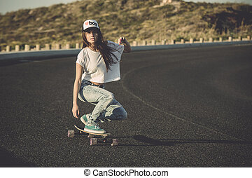 Skater girl making dowhill - Young woman making downhill...