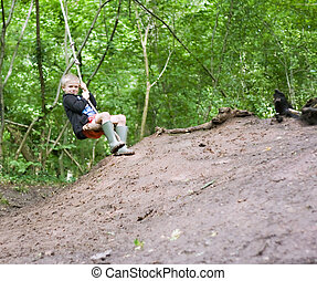 Rope swing - Young boy swinging on a rope swing in the woods