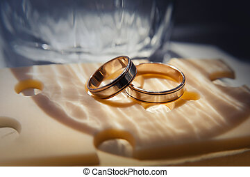 wedding rings lie on a cheese slice