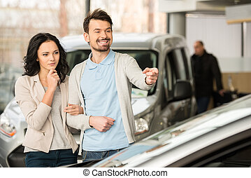 Car sales - Beautiful young couple in the showroom, choosing...