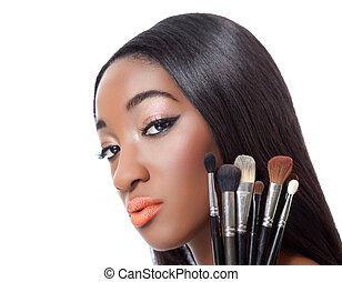 Black woman with straight hair holding makeup brushes...