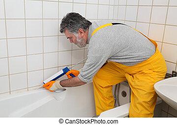 Worker caulking bath tube and tiles - Plumber caulking bath...