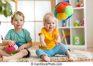 children playing with soft ball in playroom - cheerful...