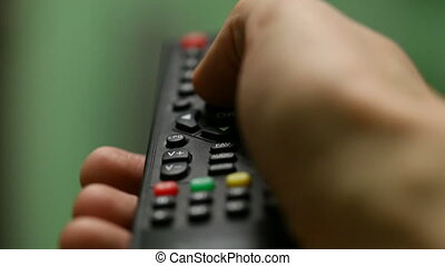remote control - Hand with remote control switches channels...