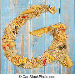Letter G made from pasta on a blue wooden background