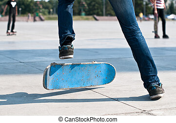 skater - young skater perfoming stunt on his blue board