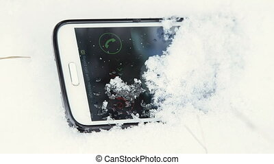 Lost cell phone ringing in the snow closeup