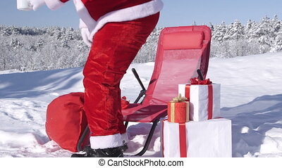 Santa Claus relaxing with cup of hot drink in lounge chair...