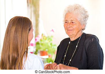 Elderly home care - Photo of young carer holding the elderly...