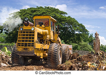 Worn bulldozer on tropical terrain - A worn, rusted and...