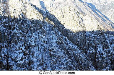 mountains and forests blanketed in snow in winter - winter...