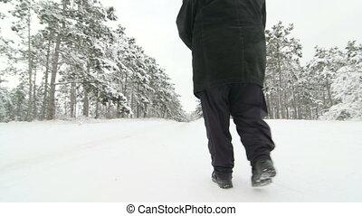 woman walking on snowy road - Elderly woman walking on snowy...