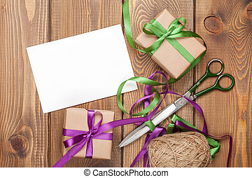 Gift wrapping with greeting card, boxes and scissors over...