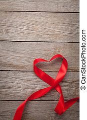 Valentines day heart shaped red ribbon over wooden table...