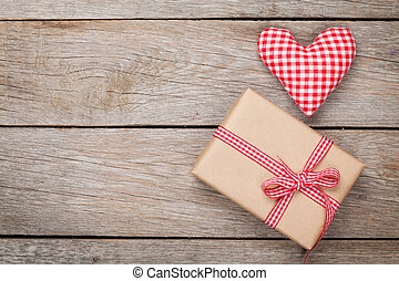 Valentines day toy heart and gift box over wooden table...