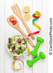 Dumbells, tape measure and healthy food. Fitness and health....