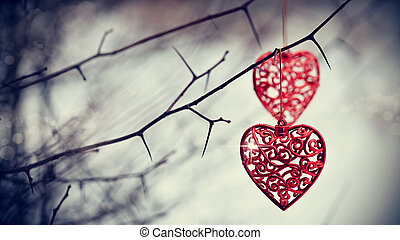 Red hearts on prickly branches. Love symbol.