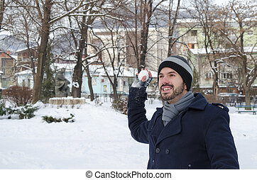 Young bearded man throwing a snowball - Young man throwing a...